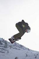 Jumping snowboarder on snowboard doing tricks, Austrian Alps, Tyrol, Tirol, Austria