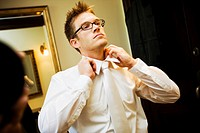 Groom, man putting on tie