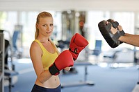 Young woman training boxing in fitness studio, eye contact