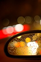 city car rearview mirror with lights and raindrops