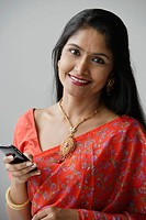 Indian woman wearing a sari and using a mobile phone