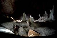 Caver exploring stalagmites in a cave