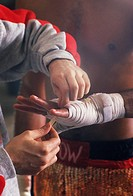 Trainer taping boxers hand