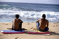 Two teens sitting on their boogie boards watching the waves