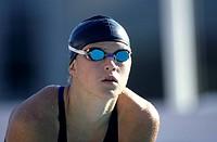 Swimmer in a black swim cap and goggles