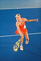 woman in red sportswear playing indoor tennis