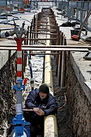 Technician of the Ludwigsburg City Works tightens a water connection in a ditch for new gas and water supply pipes in Ludwigsburg, Baden-Wuerttemberg,...
