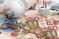 Energy saving bulb and a plug on Euro bank notes and Euro coins, energy prices