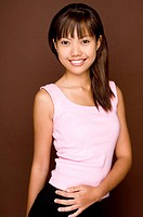 A cute young asian woman in a pink top on brown background