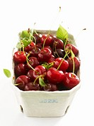 Fresh cherries with leaves in cardboard punnet
