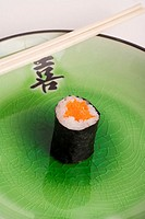 Stock photo of a single carrot vegetarian roll on a decorative Japanese green plate with chopsticks on top of the plate Mocking deprivation while diet...