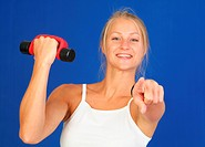 young blond woman trains with dumbbells, points toward the camera
