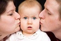 family portrait, parents kissing baby
