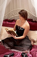 woman dressed in an evening gown and pearls reading a book
