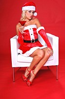 sexy blond Mrs Santa sitting in a white armchair and relaxes with a fresh Christmas Martini