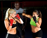 two beautiful young female fighters working with their trainer in an MMA gym