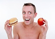 happy young man with hamburger and apple
