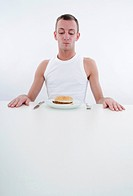 man with hamburger at plate