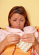 sick woman with pills lying in bed