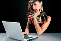 Attractive brunette fashion woman with laptop over black
