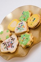Freshly baked homemade Christmas holiday cookies on a modern gold plate with curled edges