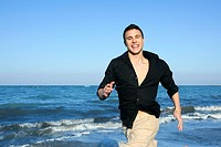 Man running happy on the blue summer beach, sunny summer