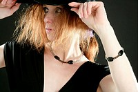 beautiful redhead woman in black with hat and jewels