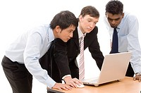 Three businessmen confer around a laptop computer