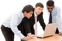 Three businessmen confer around a laptop computer