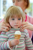Beautiful toddler blond little girl eating ice cream, mother taking care