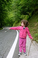 Cute little girl in a forest road dress in pink