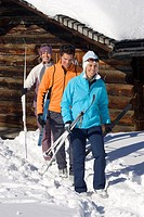 three cross_country skiers with equipment in front of an alpine hut, Austria