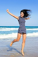 Beautiful summer brunette girl jumping on the blue beach