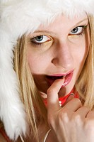 young blond woman wearing a fur cap, chewing on her finger