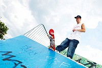 male teenager with his skateboard on a halfpipe