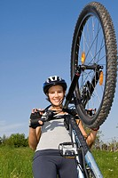 young pretty woman with mountainbike and helmet, lifting the front wheel of her bike