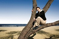 girl on a tree on the beach