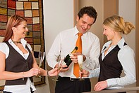 three young business people drinking sparkling wine
