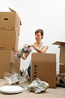 Woman packing glasses/plates in boxes