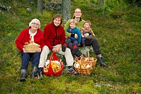 Family with mushroom baskets in forest
