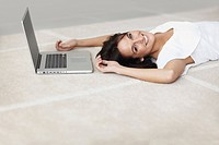 Happy woman lying on floor by her laptop
