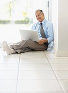 Businessman with laptop sitting on floor