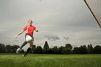 Woman kicking soccer ball