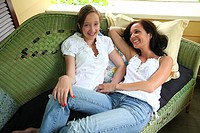 Mother and daughter laying on sofa on front porch bonding and posing for portrait