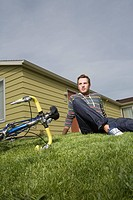 Serious man sitting on grass in front yard of home with bicycle