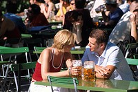 Couple drinking beer in the beer garden near Chinesischer Turm, Chinese Tower in the Englischer Garten, English Garden in Munich, Bavaria, Germany