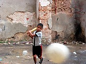 boy playing baseball in a backyard in the old town, Cuba, La Habana