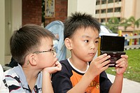 Boys playing Gameboy, Singapore, Southeast Asia