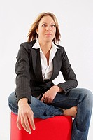 casual fair_haired woman sitting on a red cube