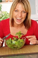laughing woman eats green salat out of a bowl